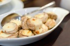 блюдо испеченных champignons грибов с расплавленным сыром в специальной плите белого цвета Стоковое Фото