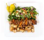 Блюдо протыкальника kebab свинины с картошками и салатом Стоковое Фото