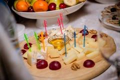 Блюдо сыров натюрморта с гайками и виноградинами Плита сыра, который служат с гайками и медом Вкусная холодная закуска диск с стоковая фотография