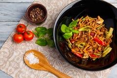 Блюдо традиционного китайския на круглой плите, лапшах риса, капусте капусты зеленой и зажаренных овощах, красных томатах вишни Стоковые Изображения RF