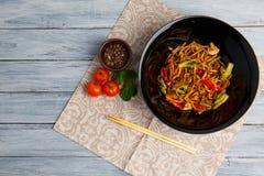 Блюдо традиционного китайския на круглой плите, лапшах риса, капусте капусты зеленой и зажаренных овощах, красных томатах вишни Стоковое Фото