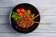 Блюдо традиционного китайския на круглой плите, лапшах риса, капусте капусты зеленой и зажаренных овощах, красных томатах вишни Стоковые Фотографии RF