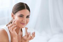 бобра Красивая женщина прикладывая сливк стороны на мягкой лицевой коже стоковое фото rf