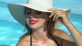 Богатая женщина в большом белом положении шляпы в бассейне, роскошном курортном отеле, здоровье акции видеоматериалы