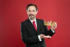 Богатое вознаграждение Зрелое вознаграждение кроны показа бизнесмена на красной предпосылке Босс Successfil большой награждая поб стоковое изображение