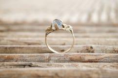 Богато украшенное обручальное кольцо на картине с естественными деревянными ручками, линиями картиной сделанной из естественных д стоковые фотографии rf