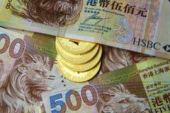 Богатство - золотая монетка и доллар Гонконга Стоковые Изображения