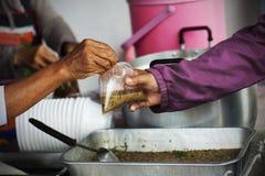 Богатые человеки дают еду к бедным концепция голодания Стоковые Изображения RF