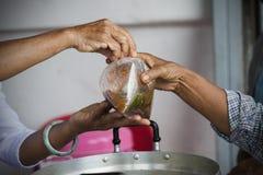 Богатые человеки дают еду к бедным концепция голодания Стоковая Фотография