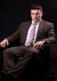 Богатый бизнесмен сидя на кресле Стоковая Фотография