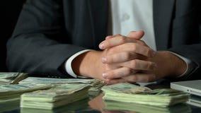 Богатый бизнесмен сидя перед пачками доллара, рост интереса депозита сток-видео