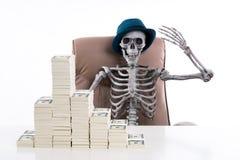 Богатый скелет положил вверх руку и стог счетов помещенных на w Стоковое Фото