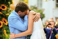 Богатый стильные groom и невеста целуя около свода солнцецвета Стоковая Фотография