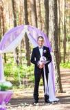 Богатый стильный groom с невестой bridal букета ждать около свода свадьбы Стоковая Фотография