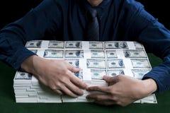 Богатый человек обнимая пачки долларов Стоковое Изображение RF