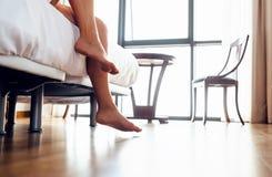 Бодрствование вверх по женщине - близким поднимающим вверх ногам женщины изображения в спальне Стоковые Изображения