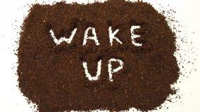 Бодрствование вверх сказало по буквам вне в земном кофе на белой предпосылке стоковая фотография rf