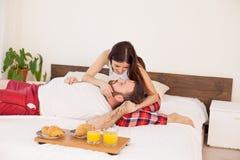 Бодрствование супруга и жены вверх в утре в завтраке выходных спальни в кровати стоковое изображение rf