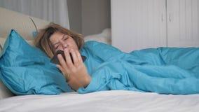 Бодрствования женщины действительно спать вверх и взгляды на телефоне бросают его и понижаются уснувший стоковые фотографии rf