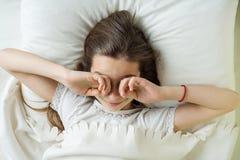 Бодрствования ребенка девушки вверх, трут глаза Лежащ на подушке в кровати, взгляд сверху Стоковое Изображение RF
