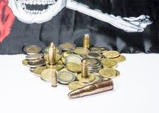 Боеприпасы и монетки рядом с флагом пирата стоковые изображения