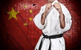 Боец карате в флаге кимоно и фарфора Стоковые Фото