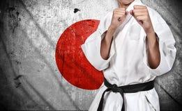 Боец карате и флаг Японии Стоковые Фотографии RF