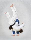 2 бойца judokas воюя людей на сером цвете Стоковая Фотография RF