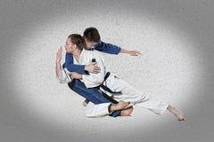 2 бойца judokas воюя людей на сером цвете Стоковое Изображение RF