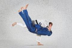 2 бойца judokas воюя людей на сером цвете Стоковые Изображения RF