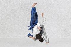 2 бойца judokas воюя людей на сером цвете Стоковые Фото
