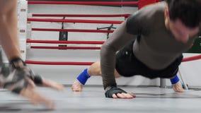 Бойцы делают нажимают поднимают с хлопами на поле на тренировке на ringside сток-видео