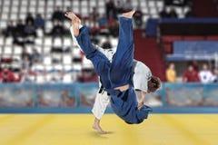 Бойцы Judokas воюя людей на предпосылке вентиляторов Стоковая Фотография