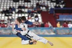 Бойцы Judokas воюя людей на предпосылке вентиляторов Стоковые Фотографии RF