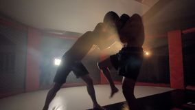 Бойцы Muttahida Majlis-E-Amal sparring в кольце в темноте движение медленное видеоматериал