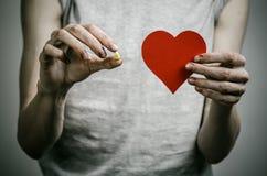 Бой против лекарств и темы наркомании: addict держать наркотические пилюльки на темной предпосылке Стоковая Фотография