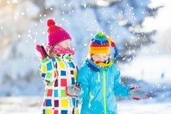 Бой шарика снега зимы детей Игра детей в снеге Стоковая Фотография RF