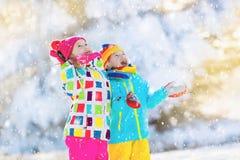 Бой шарика снега зимы детей Игра детей в снеге Стоковые Фото