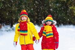 Бой шарика снега зимы детей Игра детей в снеге стоковая фотография