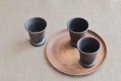 Бокалы глины темные коричневые и круглая землистая плита на грубой homespun предпосылке стоковые фотографии rf
