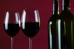 Бокалы и бутылки против красной предпосылки Стоковые Фотографии RF