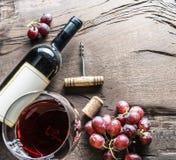 Бокал, бутылка вина и виноградины на деревянной предпосылке Животики вина Стоковые Фото