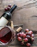 Бокал, бутылка вина и виноградины на деревянной предпосылке Животики вина Стоковое фото RF