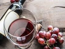 Бокал, бутылка вина и виноградины на деревянной предпосылке Животики вина Стоковое Изображение