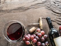 Бокал, бутылка вина и виноградины на деревянной предпосылке Животики вина Стоковое Изображение RF