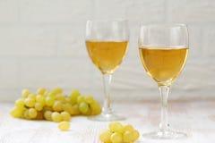 Бокал вина и виноградины в корзине на деревянном столе Стоковое Фото