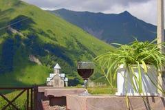 Бокал вина на ландшафте предпосылки с церковью и горами Стоковое Фото
