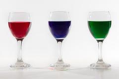 3 бокала с водой цвета разливают на белой предпосылке w Стоковые Изображения RF