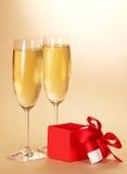 2 бокала с шампанским и подарком Стоковая Фотография
