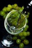 Бокал вина, виноградины, вино, пропуская от бутылки, черная предпосылка Стоковая Фотография RF